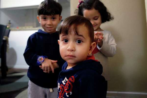 Syrian refugee Mohammad word al Jaddou, front, stands in front of his siblings twins Maria, right, and Hasan at their apartment in Dallas in November. The 30-year-old al Bashar al Jaddou decided to leave Syria in 2012 after his family's home in Homs was bombed and there was nowhere safe left to live.