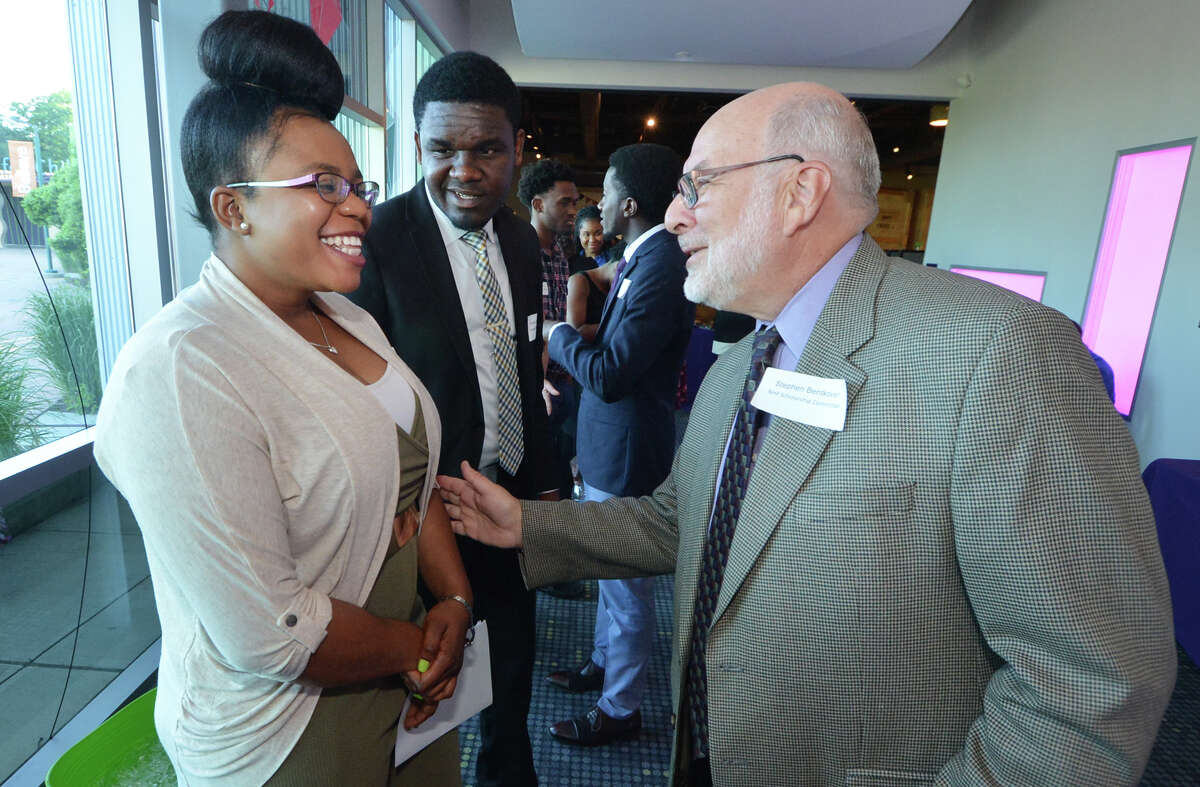 Edna Hilaire is congratulated by scholarship committee member Stephen Bentkover during the Norwalk Housing Foundation 18th Annual Scholarship Awards Ceremony at Stepping Stones Museum for Children on Wednesday June 22, 2016 in Norwalk Conn.