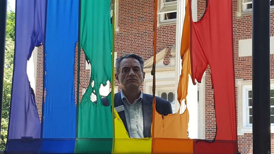 In a photo posted on the Damien Center's Facebook page, center Executive Director Perry Junjulas stands before the center's pride flag, which was set on fire early Thursday morning, according to the center's Facebook page.