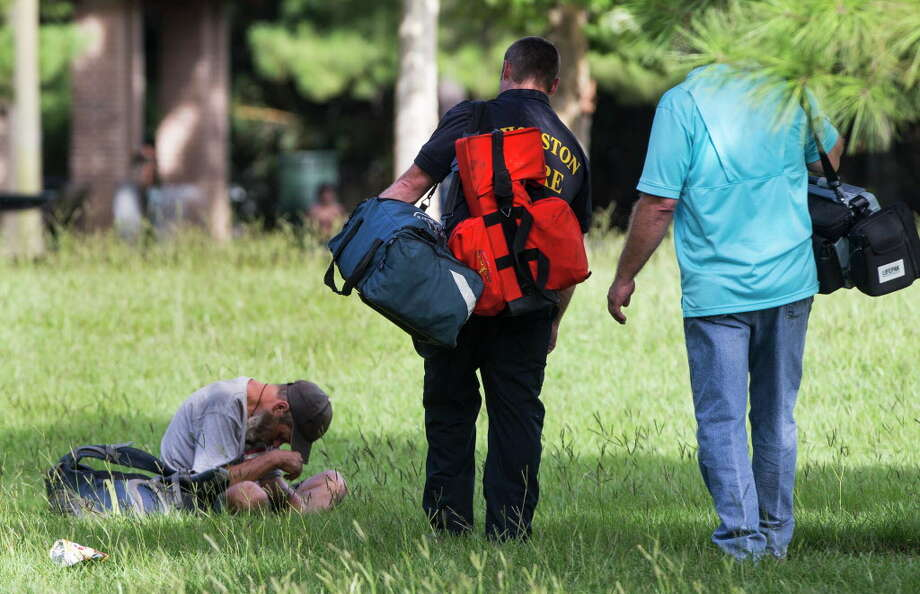 Emergency personnel check on a man seated in Hermann Park near the location where at least 12 people were taken to the hospital for a Kush overdose on Thursday, June 23, 2016, in Houston. Photo: Brett Coomer, Houston Chronicle / © 2016 Houston Chronicle