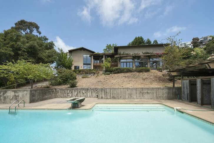 A retaining wall separates the pool from the sloping backyard at 92 Gravatt Dr. in Oakland's Claremont Hills.