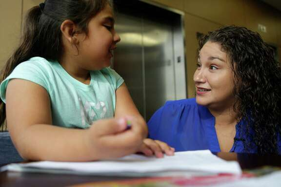 Lisa Alamia jokes with her youngest daughter, Kylie, 8, Houston Methodist Sugar Land on Thursday. Alamia developed a British accent after surgery.