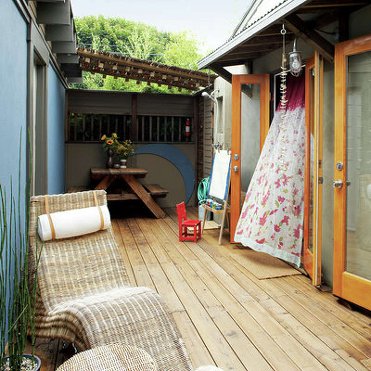 Playroom outdoors Before this deck went in, this area between the main house and garage was a repository for old appliances and other discards. Now it's a fun place to relax. The wicker chairs, seashell mobiles, and corrugated tin awnings were inspired by the homeowner's vacation in Costa Rica. More about this amazing makeover