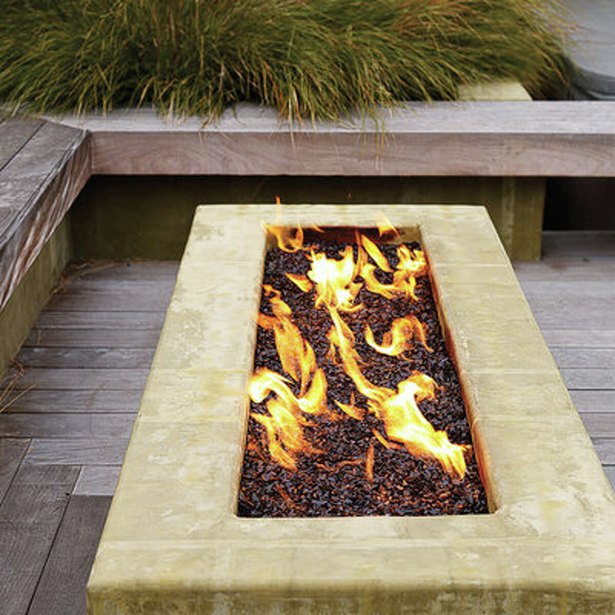 Warming firepit A raised concrete trough filled with recycled glass keeps the dining deck warm on cool nights. When not in use, the gas firepit can be covered with a slab of ipe wood, which converts it into a coffee table.