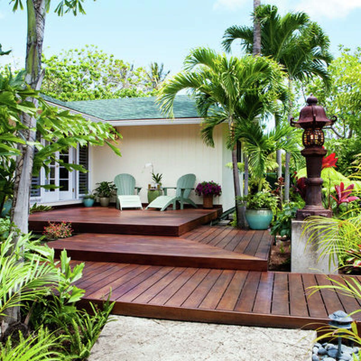 Front-yard entry deck Instead of stairs, a three-level deck steps up to the front door of this raised post-and-pier-house on the island of Oahu. Tropical accessories on the deck and throughout the garden turned this entry into a personal paradise. More about this front yard