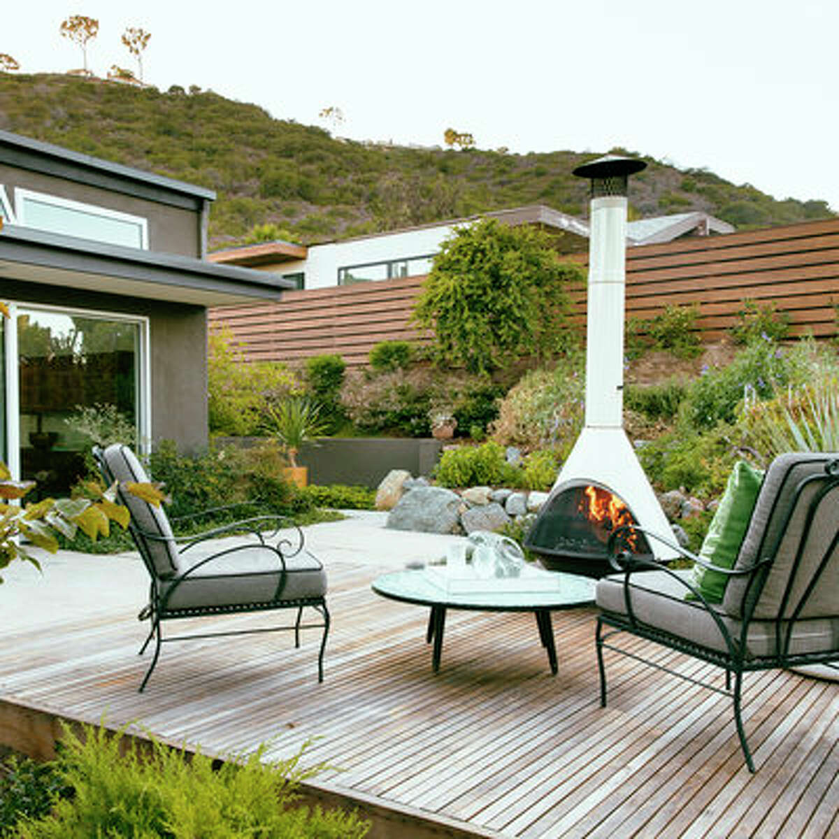 Cozy gathering space This mid-century home's deck was built from plans in Sunset's How to Build Decks for Outdoor Living, published in 1972. Large sliding doors open from the kitchen onto the space featuring a chic outdoor cone fireplace, where guests tend to migrate after dinner.