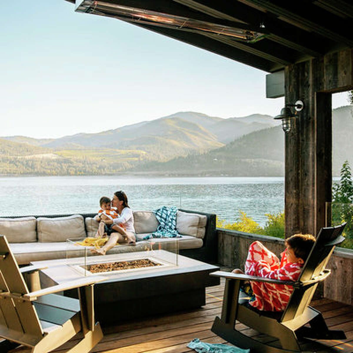On the water At this stunning lakeside home, a barely visible frameless glass rail makes deck dwellers feel as though they're perched on the prow of a ship. The home designer outfitted the space with a sofa, fire table, and rockers.