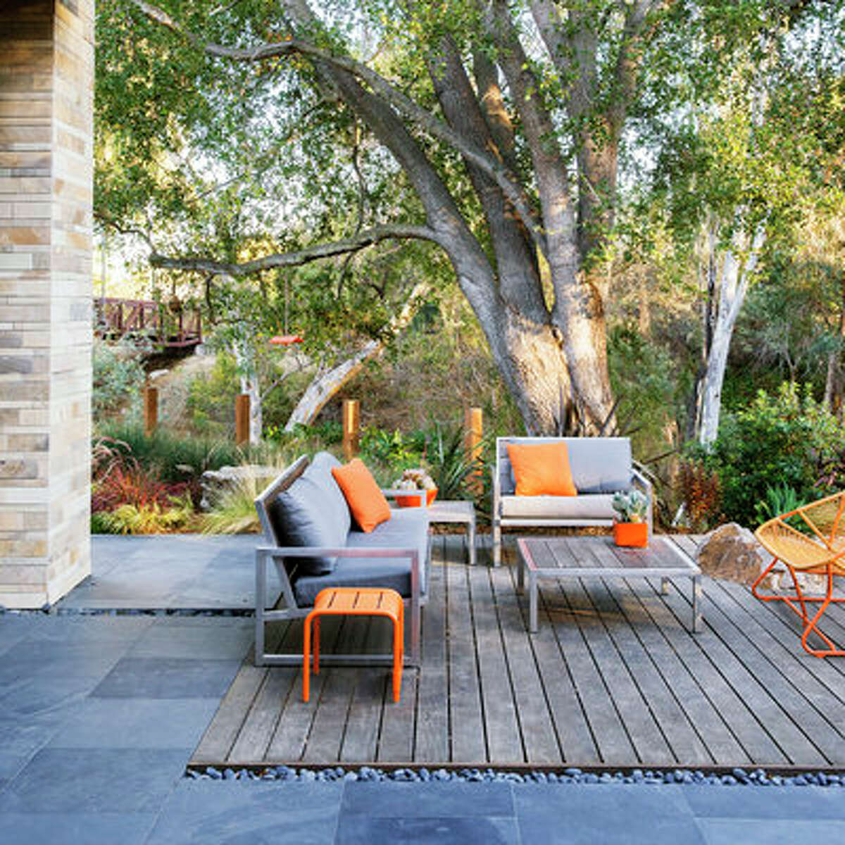 Colorful character This ipe wood deck is flush with the black slate floor extended from inside the home. The dark flooring creates the perfect backdrop for contrasting pops of bright orange.