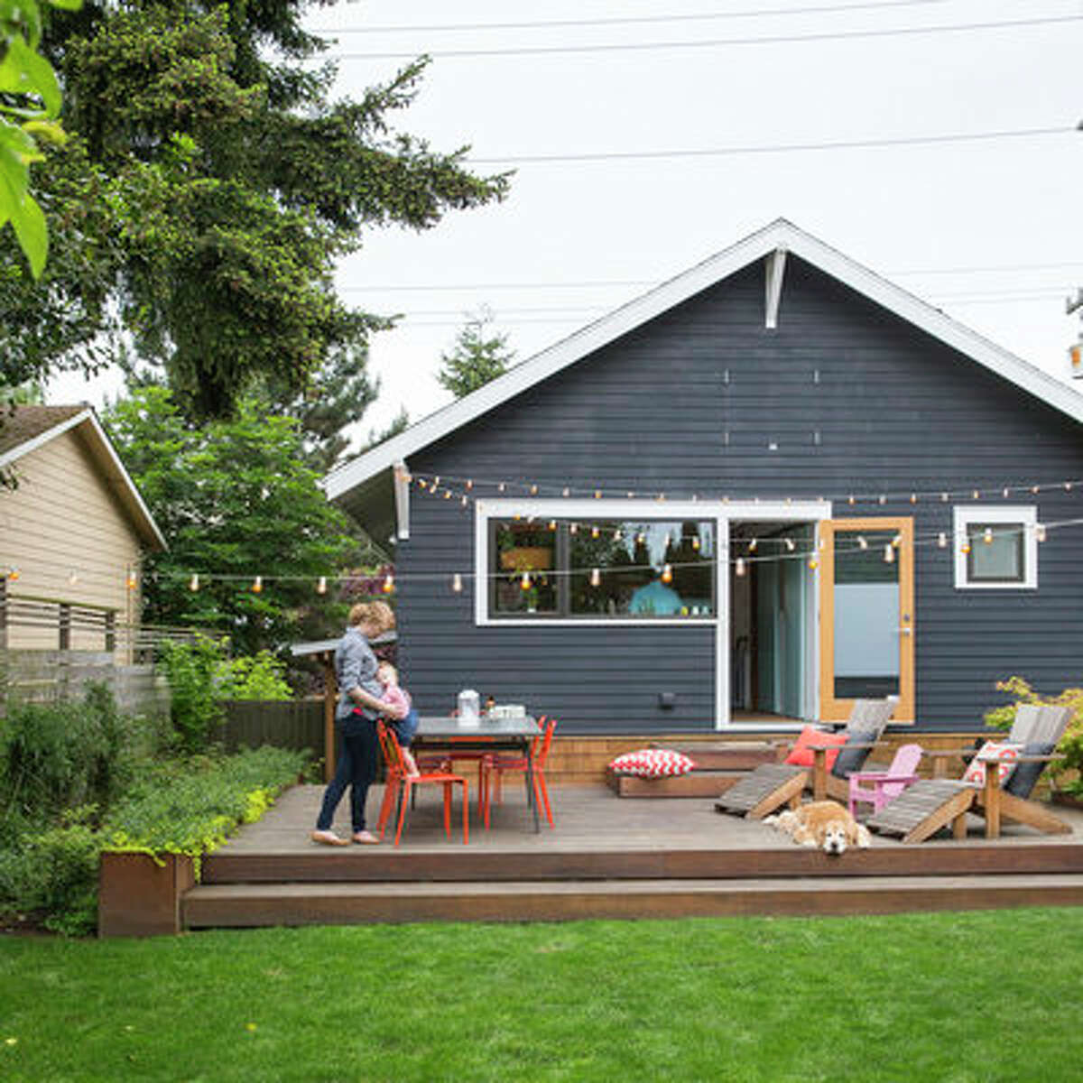 Live outdoors With interior space at a premium, these homeowners make the most of their backyard that effectively doubles their living space. With the big kitchen window and glass door (which is typically left open on nice days), they consider it an extension of their great room. During the summer, they do a lot of al fresco dining, hosting friends for barbeques, and lots of time playing with their child and dog. In addition to the expansive deck, there's a grassy play area surrounded by northwest-friendly plants, and a veggie garden planted in the strip of their