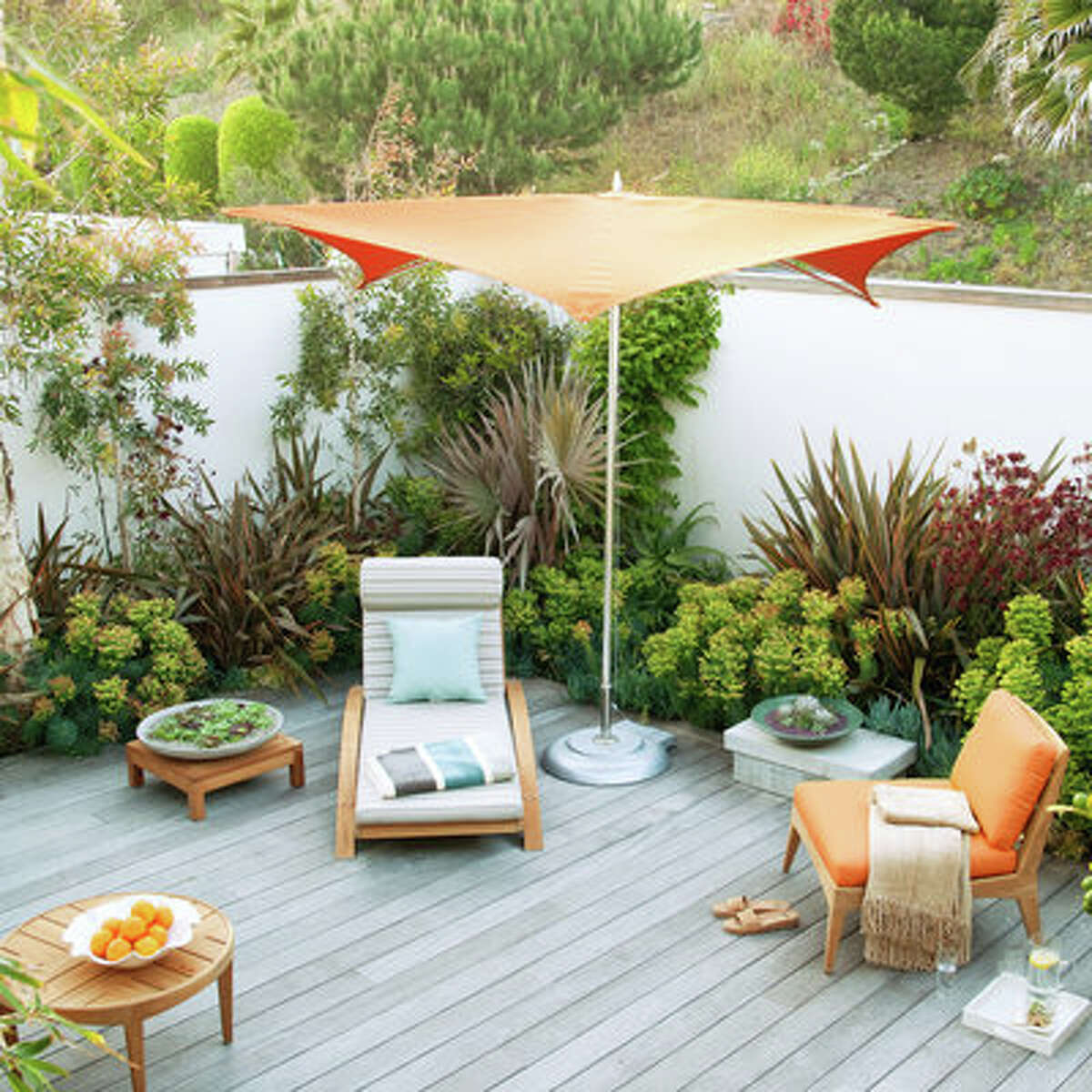 Staycation Bring out the striped cushions and colorful umbrellas, and get transported to a dream vacation spot right in your backyard. The deck is made of sustainable ipe wood that has weathered to a soft gray. Drought-tolerant plants need only yearly trimming and occasional watering-which leaves plenty of time to kick back on a lounge chair and bask in the sun.