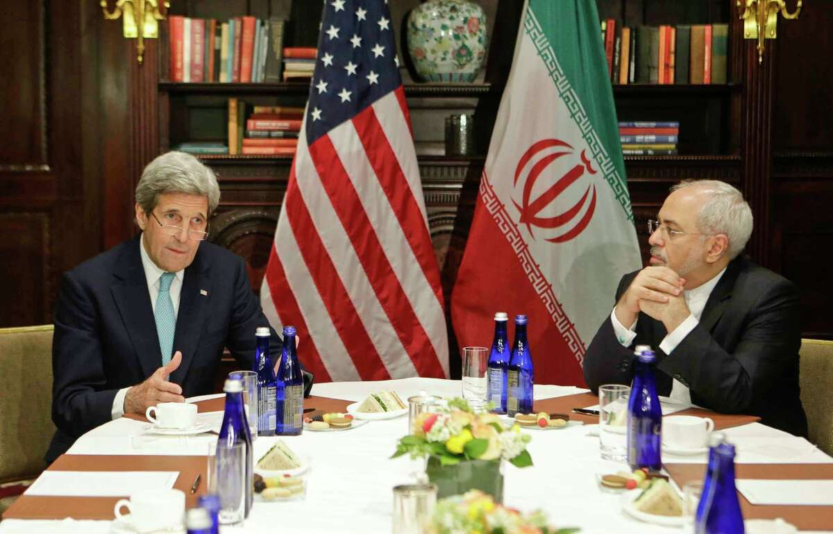 Secretary of State John Kerry speaks to the media as Iranian Foreign Minister Mohammad Javad Zarif listens.