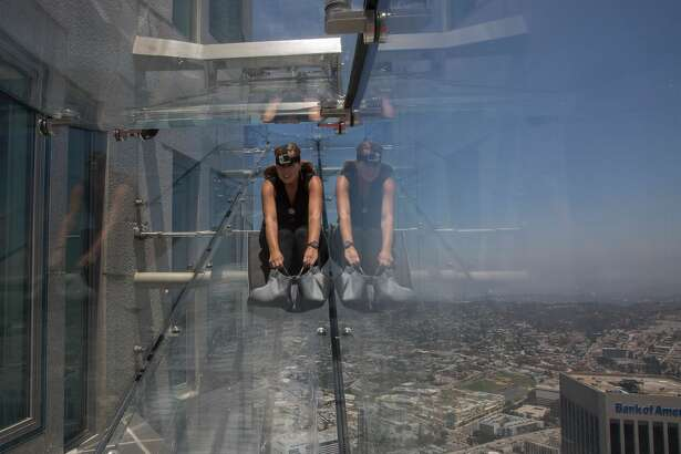People slide down the Skyslide, a 45-foot (13.7-meter) glass slide 70 floors up on the outside of the US Bank Tower, on June 23, 2016 in Los Angeles, California, during a preview the opening of the attraction.  / AFP / DAVID MCNEW        (Photo credit should read DAVID MCNEW/AFP/Getty Images)