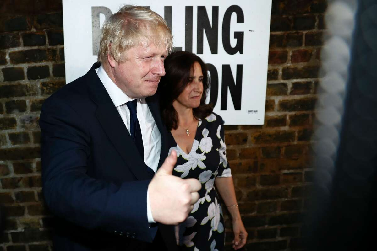 Former London Mayor and Vote Leave campaigner Boris Johnson (L) and his wife Marina Wheeler pose for the media outside a polling station in north London on June 23, 2016, as he casts his vote in a national referendum on whether to remain in, or to leave the European Union (EU). Millions of Britons began voting Thursday in a bitterly-fought, knife-edge referendum that could tear up the island nation's EU membership and spark the greatest emergency of the bloc's 60-year history.