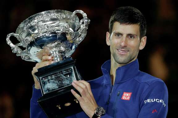 FILE - In this Jan. 31, 2016, file photo, Novak Djokovic of Serbia holds his trophy aloft after defeating Andy Murray of Britain in the men's singles final at the Australian Open tennis championships in Melbourne, Australia. If Novak Djokovic wins Wimbleon and the U.S. Open to complete a true Grand Slam, he'll have a fan in the last man to do it. Rod Laver knows what it takes to complete tennis' ultimate achievement, having won the Grand Slam as an amateur in 1962 and again as a pro in 1969. Since then, no man has come close. (AP Photo/Aaron Favila, File)