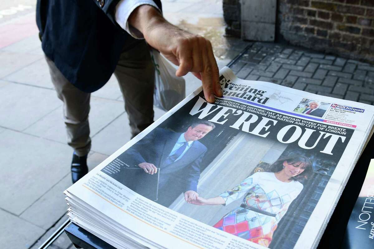A man takes a copy of the London Evening Standard with the front page reporting the resignation of British Prime Minister David Cameron and the vote to leave the EU, a decision affecting stock prices globally.