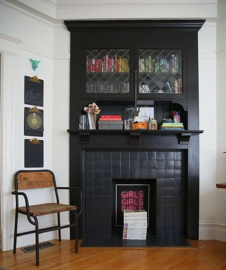 What was once a front parlor is now the office for Gina Gutierrez, who repurposes original details, like this fireplace, for her modern-day needs. Photo: Liz Hafalia, The Chronicle