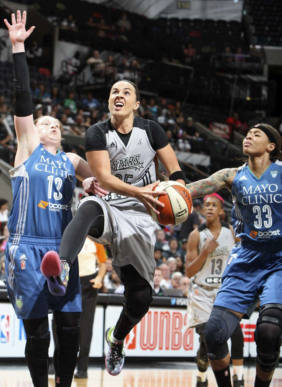 San Antonio Stars' Becky Hammon drives to the basket between Minnesota Lynx's Lindsay Whalen (left) and Seimone Augustus during first half action Saturday Aug. 23, 2014 at the AT&T Center.