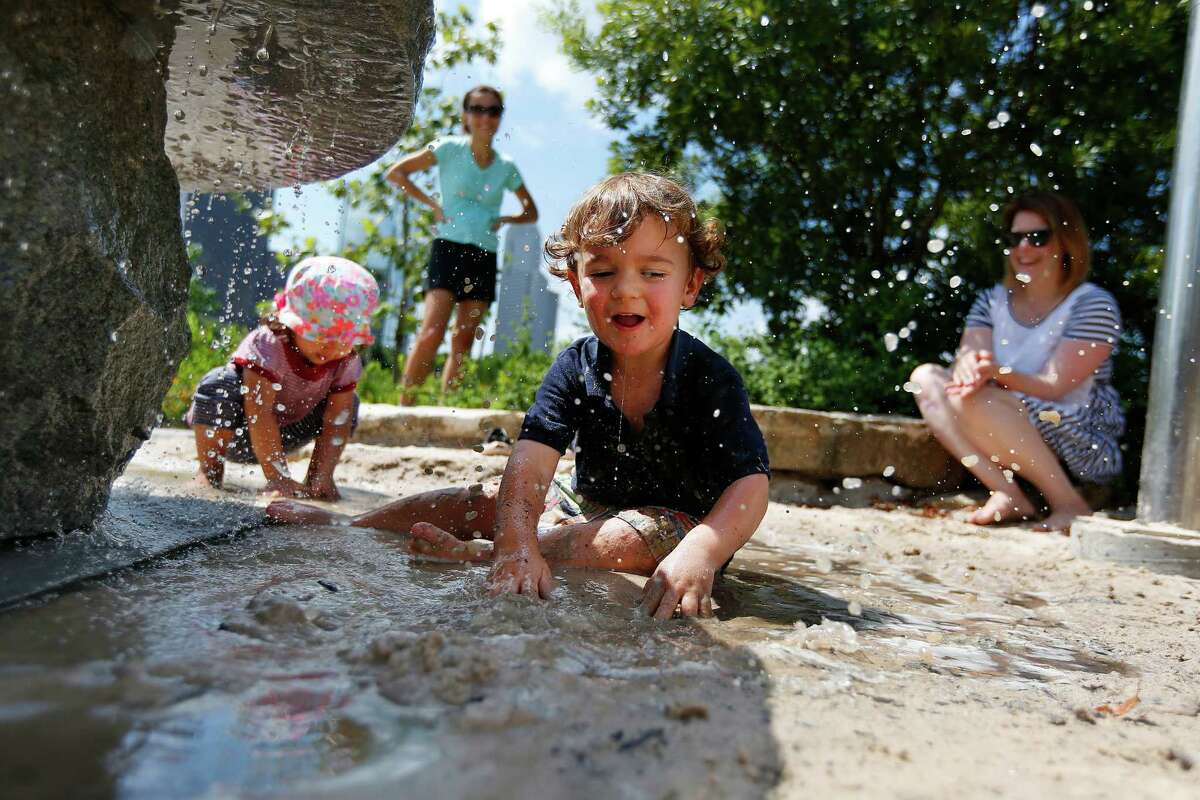Max Graber, 2, splashes in the sand beneath a stone water feature at theBarbara Fish Daniel Nature Play Areain Buffalo Bayou Park.