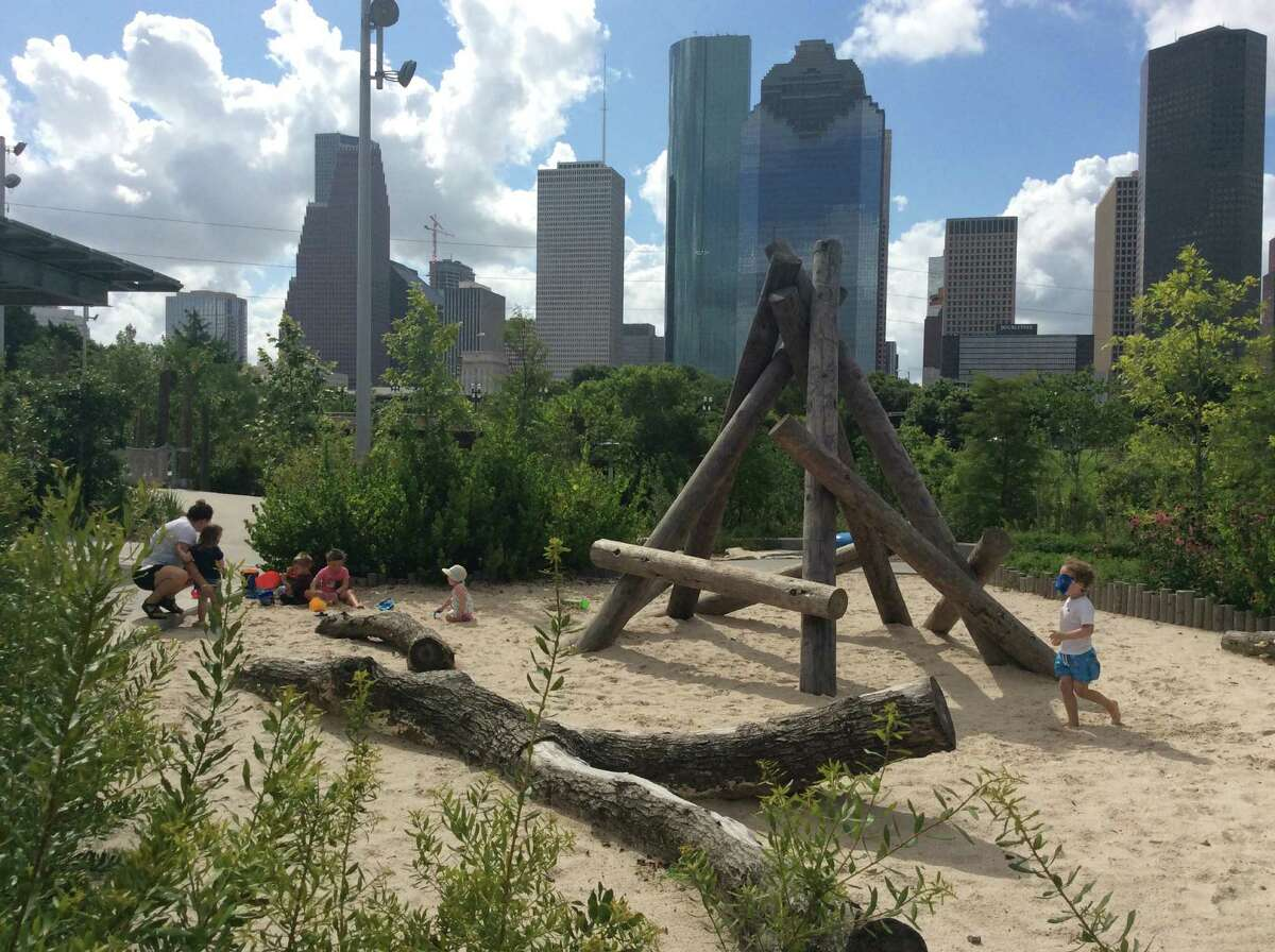 The downtown skyline provides a backdrop for play areas such as this sand pit with a teepee of logs at the park.