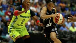 San Antonio Stars guard Moriah Jefferson (right) moves the ball around Dallas Wings guard Odyssey Sims during the first quarter of a WNBAgame in Arlington on June 23, 2016.