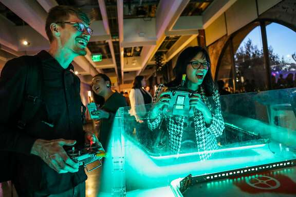 "(l-r) Ben Schwartz and Linda Pham compete against one another in a robot game, called Bash Bots, while attending a watch party for the television show ""Battle Bots"", at Autodesk offices, in San Francisco, California, on Thursday, June 23, 2016."