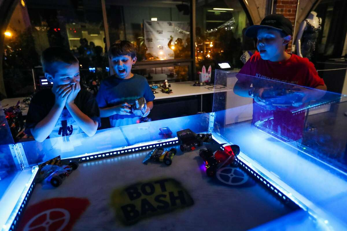"""(l-r) Declan McLaughlin, 9, Clive Potter, 8, and Edward Loski,11, compete against one another in a robot game, called Bash Bots, while attending a watch party for the television show """"Battle Bots"""", at Autodesk offices, in San Francisco, California, on Thursday, June 23, 2016."""