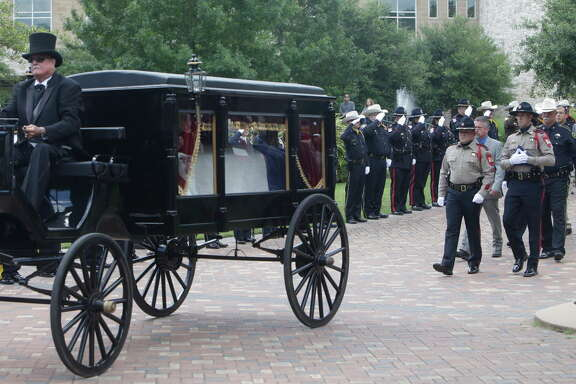 The casket of Patton Village police Sgt. Stacey Baumgartner is taken from the Woodlands Church, One Fellowship Drive,  in horse-drawn caisson after the funeral Friday, June 24, 2016, in The Woodlands.
