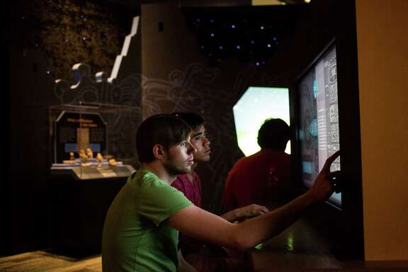 """Jacob Patterson, 22, and Daniel Perez, 26, play with an interactive game within the """"Maya"""" exhibit at the Witte Museum in San Antonio, on Tuesday, June 21, 2016."""