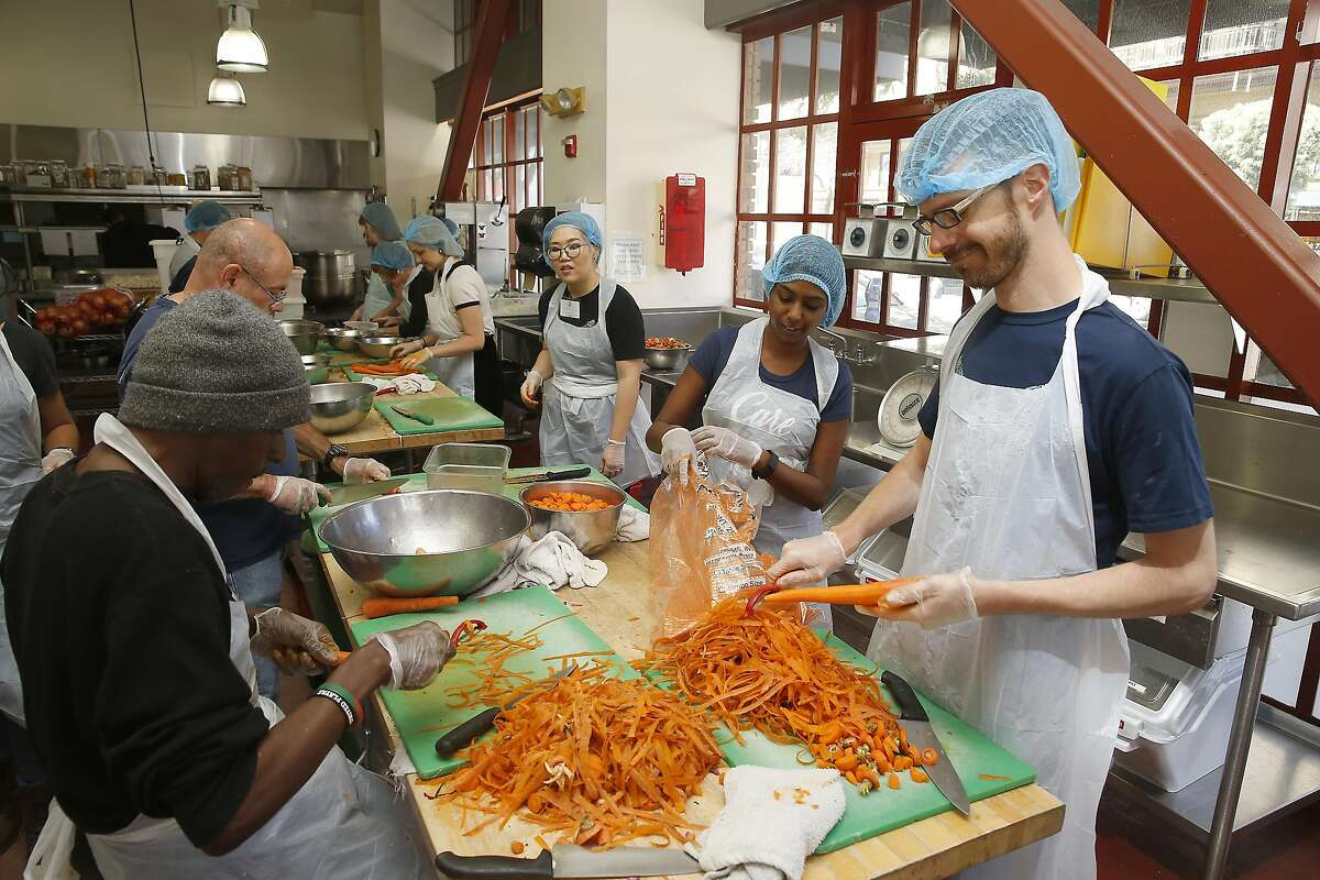 Wilshia Seeley (left) and San Francisco campaign monitors Dustin Finkle (right) and Shamita Jayakumar middle right) prep carrots in the kitchen of Project Open Hand on Friday, June 24, 2016, in San Francisco, Calif.