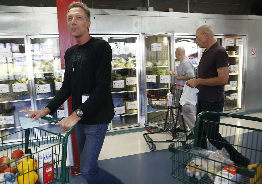 Volunteer shoppers Greg Karabeinikoff (left) and Richard Melnick get listed items for clients at the grocery center at Project Open Hand on Friday, June 24, 2016, in San Francisco, Calif. Photo: Liz Hafalia, The Chronicle