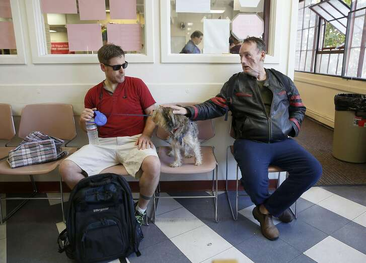David Warnecke (right) pets Rocco (middle) as they wait for food at the grocery center and kitchen at Project Open Hand on Friday, June 24, 2016, in San Francisco, Calif.  Owner of Rocco (left) accepts photo but does not want to be identified.