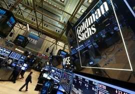 FILE - In this Aug. 15, 2014, file photo, a lighted sign marks the Goldman Sachs trading post on the floor of the New York Stock Exchange. Goldman Sachs, known for financing mega-deals and servicing the ultra-wealthy, is now open to the general public. And its interest in the average American appears to be mutual as thousands of consumers have flocked to its new retail banking service (AP Photo/Richard Drew, File)