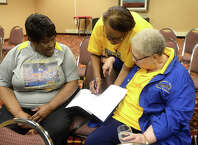 From left, Rosie Citizen, Gwendolyn Scott Walters, and Carolyn Simon look through alumni information as board members of the Hebert High School Alumni gather at the Holiday Inn in Beaumont to continue preparations for the 11th Mass Reunion celebration, which begins June 29 and runs through July 3. The event is expected to draw 800 people, with spending projected over half a million dollars. Although the school closed in 1982, its spirit is well alive, and is one of the best attended high school reunion events in Beaumont. Photo taken Thursday, June 16, 2016 Kim Brent/The Enterprise