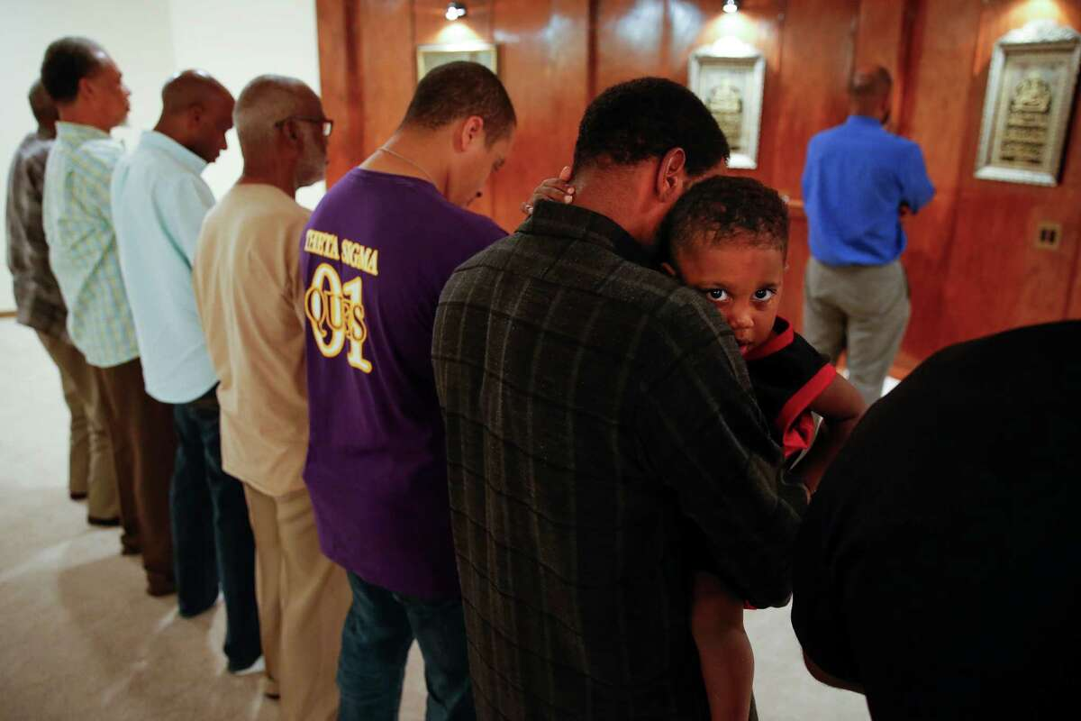 Baroque Ali, 3, looks over the shoulder of his father, Abdul Wahid Muhammad, during prayer before breaking fast during Ramadan at Masjid Warithud-deen Mohammed, Houston's oldest mosque, Monday, June 20, 2016 in Houston.