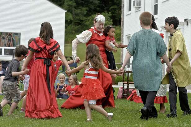 """Elyse Jasensky, director of Fairy Tale Theater, who also plays the part of Mother Goose, dances with cast members and participants from the audience during a performance last summer. Fairy Tale Theater's 2016 season opens Saturday, July 2, with the story of """"The Little Mermaid"""" on the lawn of Wooster School in Danbury."""