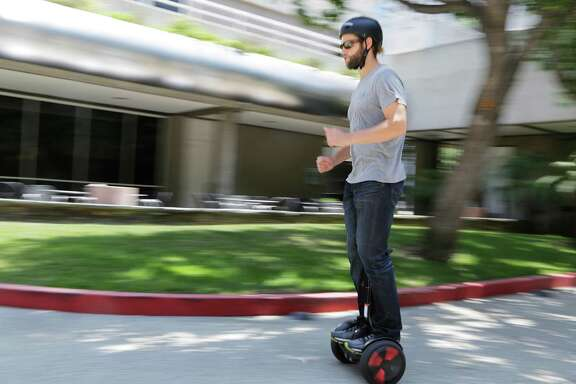 FILE - In this May 27, 2016, file photo, company representative Zach Servideo demonstrates Segway's new self-balancing scooter, the MiniPro, in downtown Los Angeles. Despite associations with fires and falls, the MiniPro comes across as a good way to make public transit more accessible if you aren't near a subway station or bus stop. (AP Photo/Reed Saxon, File)