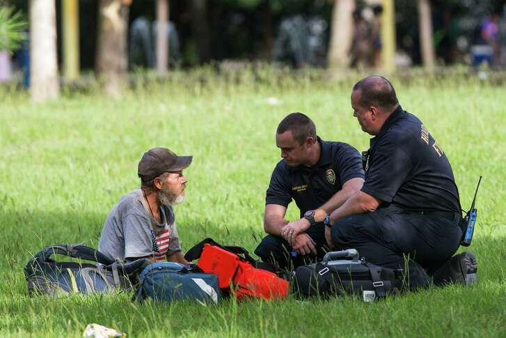 Emergency personnel check on a man seated in Hermann Park near the location where at least 12 people were taken to the hospital for a Kush overdose on Thursday, June 23, 2016, in Houston. ( Brett Coomer / Houston Chronicle )