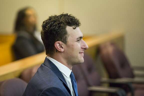 FILE - In this May 5, 2016 file photo, former Cleveland Browns NFL quarterback Johnny Manziel sits while his defense attorneys confer with the prosecution during his initial hearing in Dallas.  Manziel's representatives say the troubled quarterback was involved in a hit-and-run accident, and that the former Texas A&M star wasn't seriously injured. Manziel's publicist, Denise Michaels, said the former Cleveland player reported the incident to police, but attorney Bob Hinton says Dallas police deny that a report was filed.  It wasn't immediately clear when or where the accident happened. (Smiley N. Pool/The Dallas Morning News via AP, Pool, file)