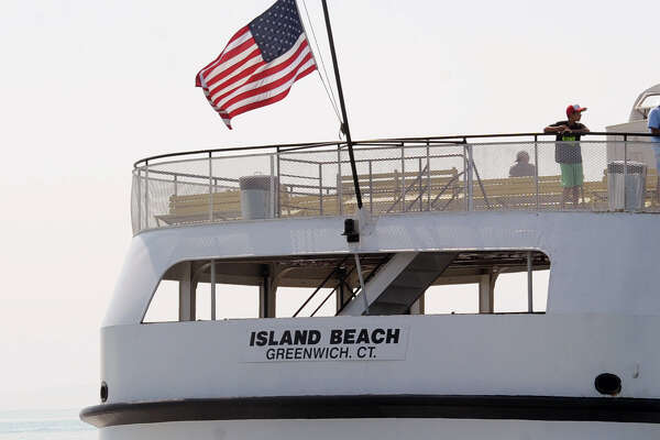 The American flag waves in the breeze from the stern of the Island Beach ferry as it makes a run to Island Beach in Greenwich.