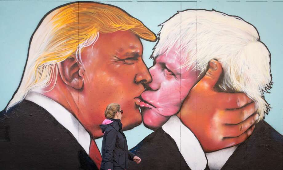 "UNITED KINGDOMA woman passes a mural that has been painted on a derelict building in Stokes Croft showing US presidential hopeful Donald Trump sharing a kiss with former London Mayor Boris Johnson in Bristol, England. Boris Johnson led the campaign for Britain to leave the European Union in a referendum which took place on June 23. Republican presidential hopeful Donald Trump has backed the so-called Brexit. Johnson's ""leave"" campaign ultimately won the Brexit vote. Photo: Matt Cardy/Getty Images"