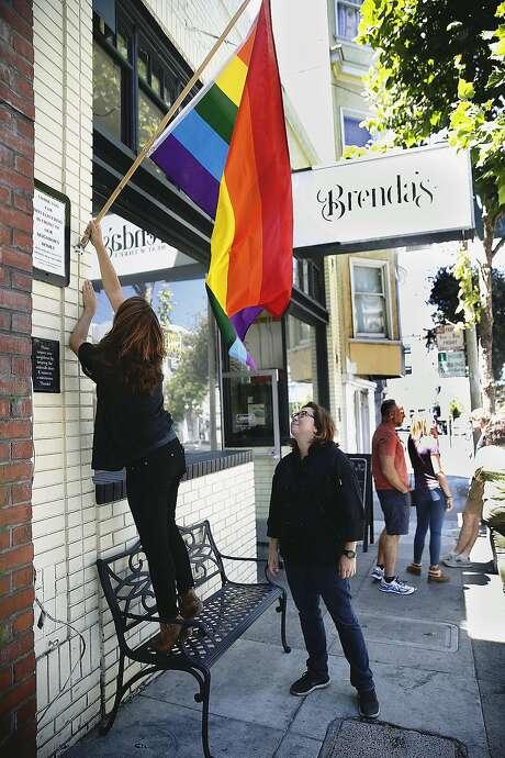 Libby Truesdell (left) places a rainbow flag with wife Brenda Buenviaje at Brenda's Meat and Three. Photo: Liz Hafalia, The Chronicle