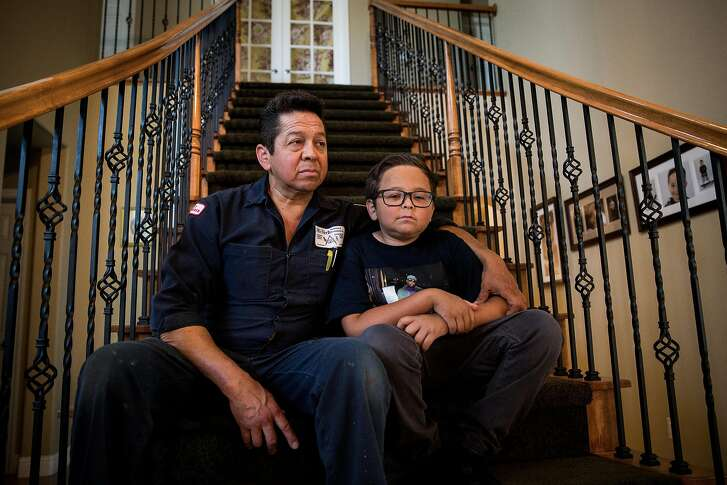 Jose Hernandez, left, and his son Jonah Hernandez, 11, pose for a portrait in their Sacramento, California home, June 24, 2016. Hernandez is struggling to keep their home after his wife, the sole owner on the title, died in 2011. Sen. Mark Leno, D-San Francisco, has a bill to require banks help senior and widowed homeowners avoid losing their homes in cases where the surviving spouse isn't on the title.
