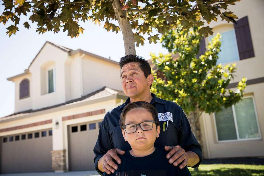 Jose Hernandez and son Jonah outside their Sacramento home, which is in danger of foreclosure with an auction date set for Aug. 15. Photo: Max Whittaker/Prime, Special To The Chronicle