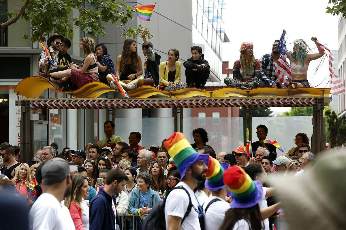 People sat and stood anywhere they could to see the SF Pride parade in San Francisco, California, on Sunday, June 28, 2015.