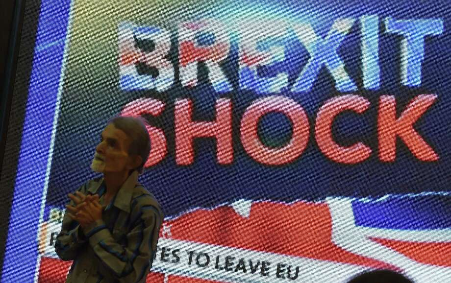 An Indian pedestrian gestures as he stands near a large screen showing news of Britain's vote to exit the European Union in Mumbai on June 24, 2016.  The pound collapsed to a 31-year low and there was pandemonium on currency, equity and oil markets on June 24 as Britain voted to leave the European Union, fuelling a wave of global uncertainty. Sterling crashed 10 percent to $1.3229 at one point, its weakest level since 1985, while the greenback itself slumped below 100 yen for the first time in two-and-a-half years as traders fled to safety.  / AFP PHOTO / PUNIT PARANJPEPUNIT PARANJPE/AFP/Getty Images Photo: PUNIT PARANJPE, Stringer / AFP/Getty Images / AFP or licensors