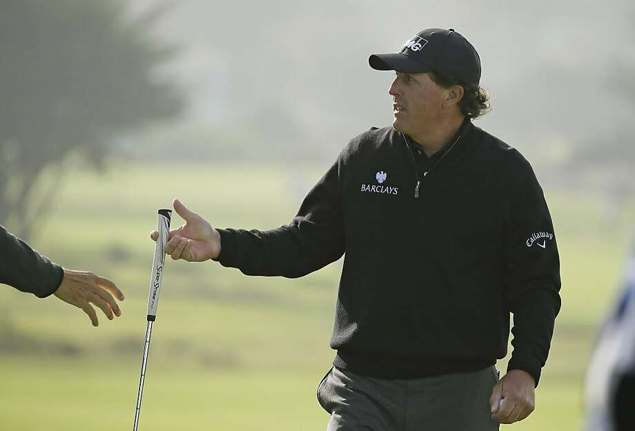 Phil Mickelson hands off his putter while walking off the sixth green of the Monterey Peninsula Country Club Shore Course during the second round of the AT&T Pebble Beach National Pro-Am golf tournament Friday, Feb. 12, 2016, in Pebble Beach, Calif. (AP Photo/Eric Risberg) Photo: Eric Risberg, AP