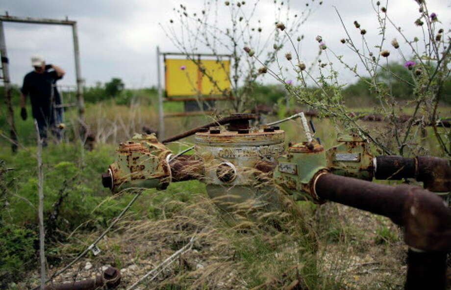 In this Friday, May 13, 2016, photo, a manifold for oil pumps sits idle on a South Texas ranch near Bigfoot, Texas. The agencies that regulate the oil and gas industry are running out of money just as some problems in the oilfields are worsening. Meanwhile, defunct companies are abandoning wells that are in danger of deteriorating. (AP Photo/Eric Gay) Photo: Eric Gay, STF / Copyright 2016 The Associated Press. All rights reserved. This material may not be published, broadcast, rewritten or redistribu