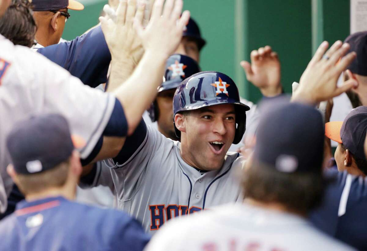 Houston Astros George Springer is congratulated in the dugout after hitting a grand slam in the first inning of a baseball game against the Kansas City Royals at Kauffman Stadium in Kansas City, Mo., Friday, June 24, 2016. (AP Photo/Colin E. Braley)