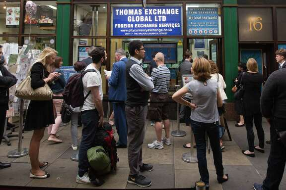 "Customer line up outside a foreign currency exchange bureau in London on June 22, 2016. There were reports of Britons seeking to buy euros and dollars ahead of the ""Brexit"" vote. (MUST CREDIT: Bloomberg photo by Simon Dawson)"