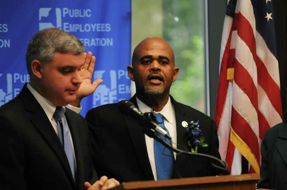 PEF President Wayne Spence is sworn in by Mario Cilento, president of the NYS AFL-CIO during the swearing-in ceremony of elected officials at the New York State Public Employees Federation headquarters on Monday, August 3, 2015, in Latham, N.Y. (Olivia Nadel/ Special to the Times Union) Photo: ON / 10032860A